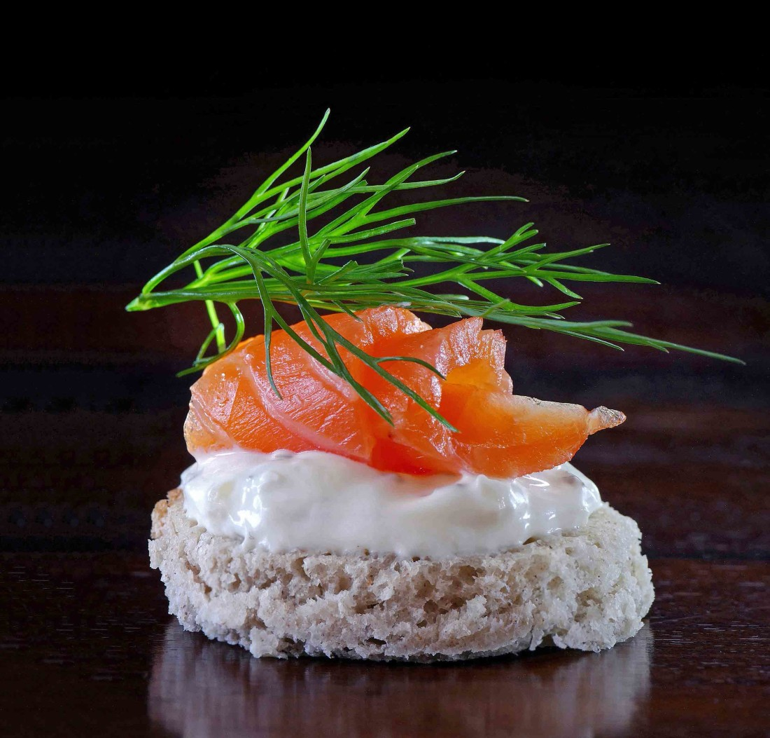 salmon canape with cream and dill  on dark wood, black backgroun