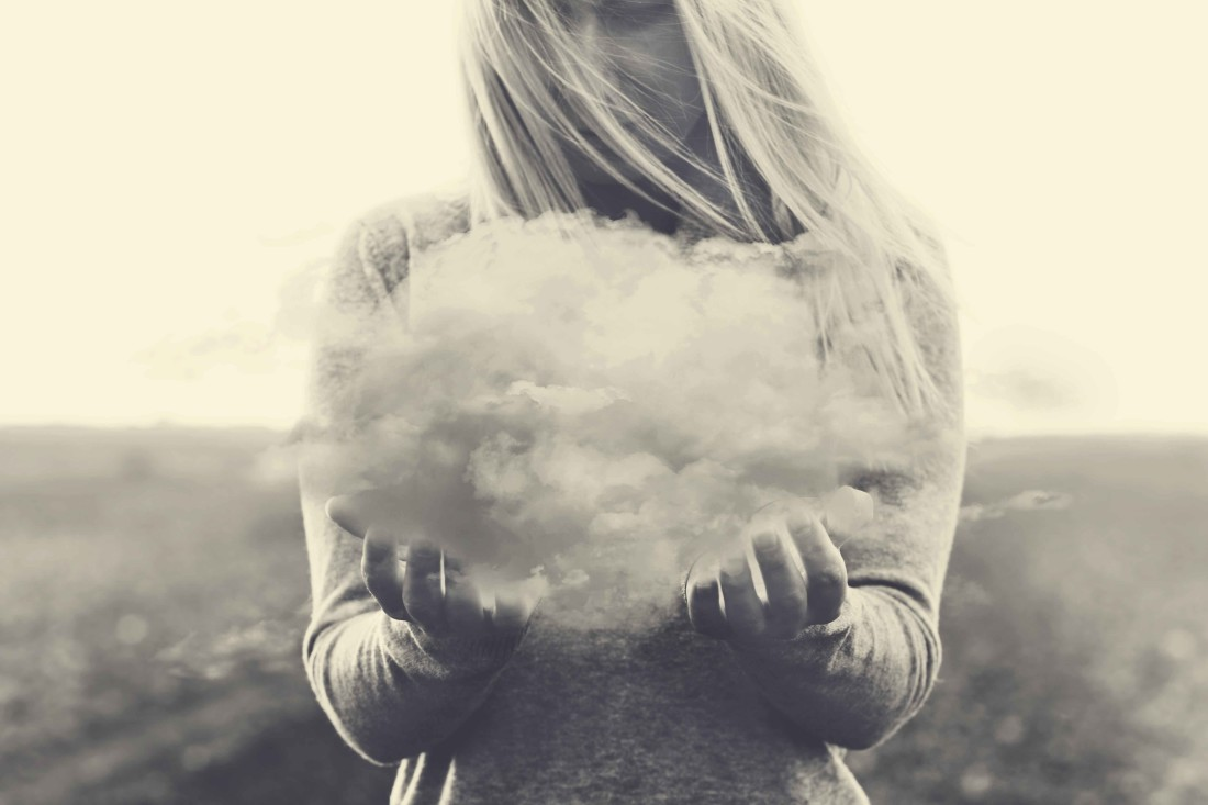 Surreal moment, solitary woman holding in her hands a gray cloud